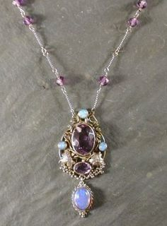 Dorrie Nossiter (attrib). Arts and Crafts pendant necklace, the central facetted amethyst surrounded by a network of vines and opal cabochons with further cut amethyst stone and cabochon opal pendant drop, the twisted link chain amethyst stone spacers. Attributed to Sibyl Dunlop as well as Dorrie by the auctioneers, but is likely by Dorrie. Lyon and Turnbull, 5 Nov 2003, £400. Adapted from a clip into a pendant, and late chain with amethysts added See…