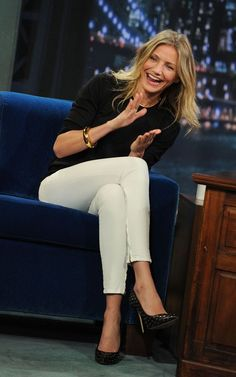 Cameron Diaz in a black 3/4-sleeve boatneck top with straight white pants, gold-studded black heels, and simple gold jewelry.