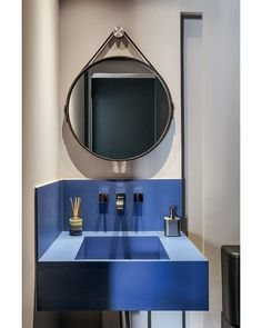 Neste projeto de 60 m² do escritório Mandril Arquitetura, a marcenaria feita sob medida faz toda a diferença. O lavabo tem bancada de Cobalto Neolith e espelho redondo da Estar Móveis (Foto: Mariana Orsi/Editora Globo) @mandrilarquitetura @estarmoveis #lavabo #bathroom #banheiro #azul #decoração #décor #decoration