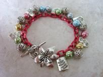 "Ingredients:  Glass pearl beads in gold, green silver, blue and pink/mauve  ""Antique"" silver tone fern, flower and filigree beads  ""Antique"" silver tone  flower clasp  Red chain (some lighting I think it takes on a dark pink cast)  This bracelet measur..."