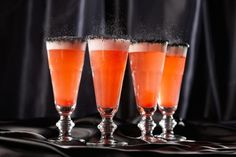"Orange Hocus Pocus Fizz. Make this with ""spirits"" or without for a great ""mocktail."" It's rum, coconut and pineapple with a ghoulish twist: black sugar on the rim!"