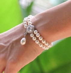 Pearl wedding bracelet in a double strand style uses Swarovski pearls with a square crystal set in a pavé halo as its center feature. Erica is a