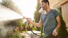 Summer morning in countryside house. Portrait of young attractive tan-skinned bearded man in blue t-shirt smiling, watering plants with hose, working in garden Recycled Rubber, Diy Garden Projects, Buyers Guide, Water Supply, Water Plants, Garden Hose, Countryside, Things To Come, Tan Skin
