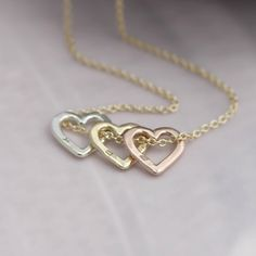 """Personalised 9ct Gold Mini Heart Necklace  A beautiful open heart necklace handmade in 9ct gold with your choice of initial handstamped on one side of the pendant. This design is an incredibly popular option to show that very special person just how much they mean to you in a discreet way. This design comes with an extra fine 18"""" extra fine 9ct gold chain in a colour of your choice and can be mixed and matched as a cluster or worn singularly. This item can be purchased with blank hearts…"""