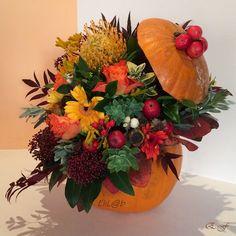Zucca di Halloween con fiori e bacche dai colori autunnali