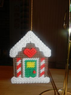 This adorable gingerbread house ornament measures approx. 3 wide x 4 high. It is backed with clear plastic canvas leaving no unsightly, unfinished backing exposed.