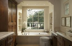 Traditional bathroom features an alcove filled with a tiled tub accented with a deck-mount tub ...