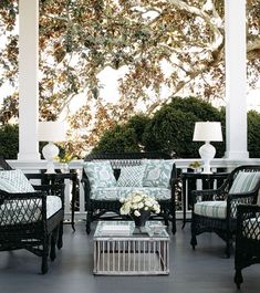 I like the dark furniture and the cool blue of the fabrics. The lamps and coffee table add a formal touch to this porch