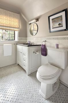 Designer Claire Paquin pays homage to old-world style and charm with the redesign of this guest bathroom in white and gray. A traditional-style white vanity with a dark countertop complements tile on the wall and floor, while the artwork, round mirror and patterned Roman shade help assert the vintage look. The room is classic, clean and comfortable.