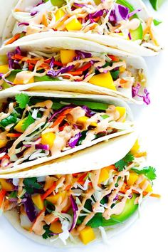 This Mango Chipotle Fish Tacos recipe is made with flaky mild fish, filled with a zesty mango slaw, and drizzled with a creamy chipotle lime sauce.