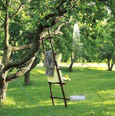 A installer rapidement au coeur du jardin sur le plus bel  arbre, une douche extérieure simplement constituée d'un pommeau de douche au bout du tuyau d'arrosage.