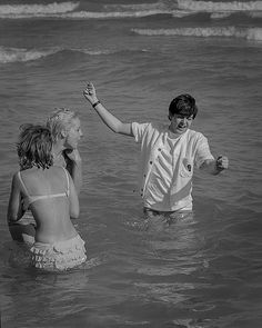 Paul McCartney in the sea at Miami Beach with a couple of girls during the band's tour of America in February 1964