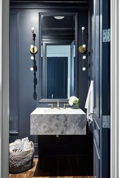 Stunning black paneled powder room is fitted with a tall black framed mirror flanked by modern brass linear sconces and hung above a marble floating sink vanity finished with a brass faucet kit. Powder Room Vanity, Vanity Room, Vanity Sink, Carrara, Black Powder Room, Half Bath Remodel, Floating Sink, Modern Powder Rooms, Wainscoting Bathroom