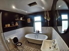 Black and white Victorian bathroom, white metro tiles with large round mirror and chunky wooden shelves and roll top bath