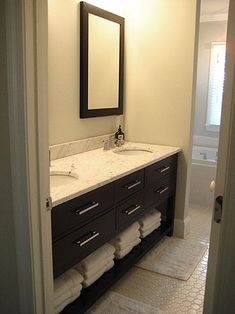 dark cabinetry with marble surface, hexagonal floor tile, subway tile on bath tub