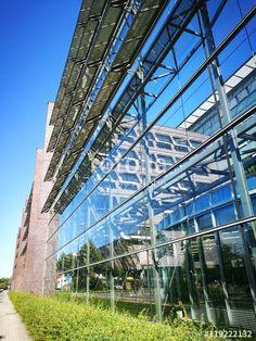 Glasfassade mit Photovoltaikanlage vor blauem Himmel eines Verwaltungsgebäudes in Münster in Westfalen im Münsterland