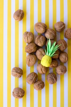 DIY Itty Bitty Pineapples. Paint Walnuts and use cardstock cut outs to make these adorable summer accent crafts!