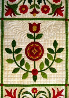 "close up, Bed of Roses: red and green quilt by Sue Garman.  She says:  ""I know that most long arm quilters don't relish doing cross-hatch quilting, but I do.... One just has to decide what looks best on a quilt.  I do that by putting a big sheet of plexiglass on top of my quilt and using a dry-erase marker to audition various quilting motifs on a quilt."""