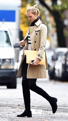 Karlie Kloss wears a tan button trench coat, striped sweater, black skinny jeans, and Stuart Weitzman over-the-knee boots