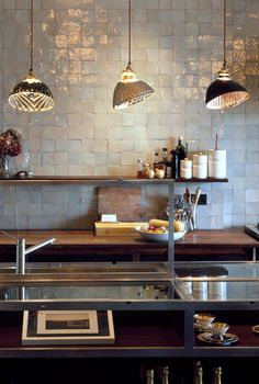 Vintage lighting and reclaimed wood surfaces contrast with contemporary tiles.