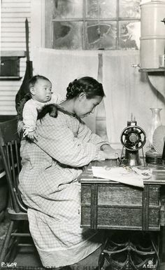 Washington State Historical Society - Photograph of a Native American woman sewing at a table with a machine and a baby on her back wrapped in fur. She is seated indoors in a well-furnished room.