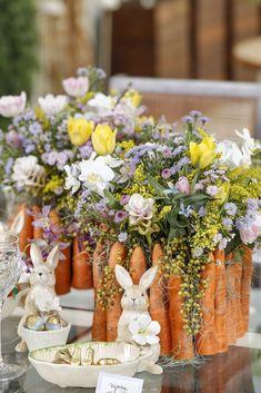 Os coelhos, símbolos de prosperidade, também aparecem comcestinhas e folhas de bananeira de porcelana byStefan Behar, cheios de minichocolatinhos e ovinhos de Páscoa para depois do almoço!