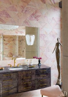 glass sconce floats over the vanity mirror in this pink marble clad bathroom // Kelly Wearstler