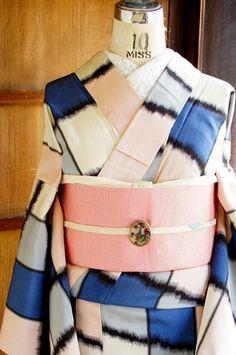 アイボリーやグレー、ペールピンクやネイビーブルーなどのマルチカラーでブロッキングされた変わり格子のようなデザインがレトロモダンな正絹御召の単着物です。