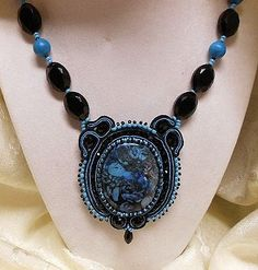 Soutache work by JMP member Gmoodify. Made with a Nipomo Blue Coral Fossil Cabochon with crystal, seed beads, and Turquoise.