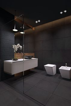 A fantastic public bathroom, combining black walls and white sanitary elements.
