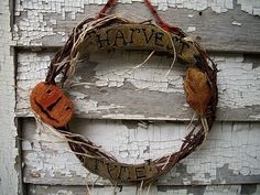 PUNCH NEEDLE PUMPKINS ON A GRAPEVINE WREATH.