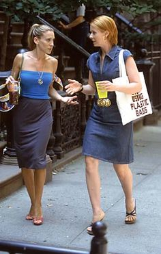 Notice both girls are wearing blue. Carrie wears her hair swept all the way back in an extreme ponytail. Walking the New York streets and talking. Only way you could get anywhere sometimes is to do two things at once.