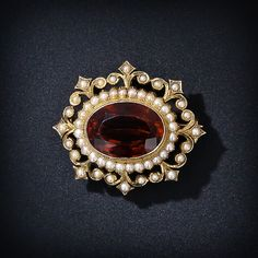 An entrancing deep golden amber color faceted citrine is regally presented with seed pearls set in a crown inspired frame. Also wearable as a pendant. Circa 1890.