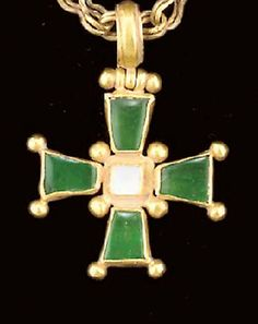 A BYZANTINE GOLD AND EMERALD PENDANT CROSS AND CHAIN Circa 5th-7th Century A.D. The cross with flaring arms radiating from a central square, a large granule between each arm and at each corner, a square section of mother-of-pearl bezel-set in the center, and emeralds set in each arm, a suspension loop above, the cross suspended on a figure-8 loop-in-loop chain with cruciform terminals formed of four large granules, ending in a modern hook and loop closure