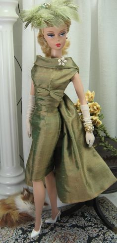 A uniquely colored silk makes a lasting impression with shimmery vintage details and elegant styling. The sheath is cut from laurel colored pure silk, fully lined, and features a portrait style collar, ruched waistline with bow detail and button over snap back closure. A detachable drape is gathering at the back and fastened with a loop of button. The matching pillbox is fully lined, and festooned with a vintage quality milliners bloom. 70.00 SHOES, JEWELS, GLOVES, SUNGLASSES, DOLL AND ...