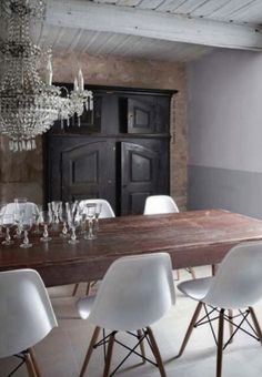 Statement chandelier with raw brick wall and Eames chairs
