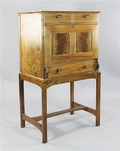 A Sussex Guild walnut escritoire by Bert Buri, reputedly made from the trees fallen in the great storm 1987, fitted an arrangement of three drawers and a folding front revealing an interior with pigeon holes and drawers, on square section legs with H frame stretcher base, marks to the back BB 1996, W.2ft 5.5in. H.4ft