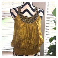 Bebe T-Back Blouse Elegant t-back blouse..mustard in color..gun metal and silver beading..there's a small rip in the collar area as shown in the picture. This blouse is so beautiful!  I've just outgrown it! Super cute with white slacks .✌️ bebe Tops Blouses