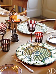 The dining tables in Vienna Hall feature plates depicting garden labyrinths and jewel-toned wine- and water glasses | archdigest.com