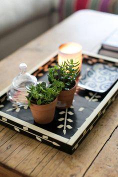 コーヒーテーブルにグラフィックが素敵なトレイを置き、小ぶりのグリーンやキャンドルをディスプレイ。