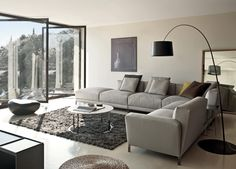 Living room Ideas: Contemporary Furniture, Leather Chairs, L Shaped Gray Sectional Sofa, Cream Walls, Round Coffee Table. Ranario