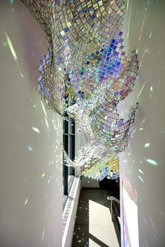 thousands of iridescent acrylic Plexiglas squares into chain link cells, Park has created a sprawling, undulating form that transmits, reflects, and refracts both the natural and artificial light