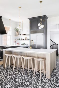 Welcoming black and white kitchen is accented with an oak center island seating light wood tractor barstools at a white quartz countertop fitted with a farmhouse sink and a polished brass gooseneck faucet lit by brass pendants.