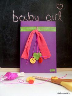 Μπομπονιέρα σε μωβ φακελάκι, με μια υφασμάτινη ροζ κορδέλα, πράσινο πουά washi tape, κρεμαστά ξύλινα κουμπάκια, και μια ξύλινη καρδιά ντυμένη σε πράσινο πουά washi tape. Τιμή: 2,00 ευρώ.