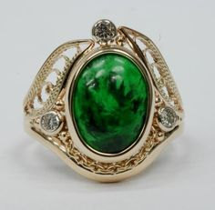 14kt yellow gold ring with Mawsitsit and diamonds. Maw-sit-sit is a unique name, and the rich emerald-green and black patterened stone lives up to it. This stone is found only in northern Myanmar.
