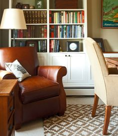 A mixture of photographs and other personal mementos on the bookshelves keep the home office cozy.