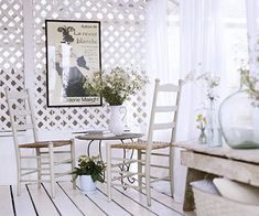 """Walls"""" of lattice hide the outside world and create a restful oasis. Sheer curtains in white cotton voice hang from curtain rods for an ethereal backdrop. A vintage poster hung on the new lattice wall creates a focal point for the homeowner's tea corner"""