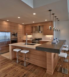 Thick slab countertop. Natural wood finished cabinets