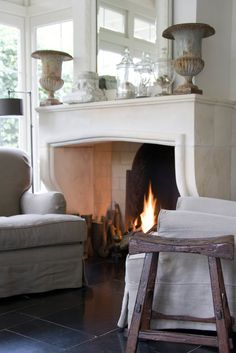White walls, fireplace, 2 slipped chairs, urns in vignette on mantle - breadandolives