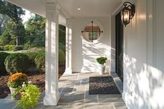 To enhance the entryway, wood paneling was installed, a new front door, added iron work to the round window and the flagstone paving was extended forward of the porch to create a more gracious entryway.